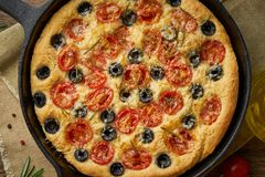 Focaccia, pizza in skillet. Close up italian flat bread with tomatoes, olives and rosemary. Top view, wooden table. Focaccia, pizza in skillet. Close up italian stock images