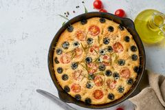 Focaccia, pizza in skillet, italian flat bread with tomatoes, olives and rosemary. Top view, copy space, white concrete background. Focaccia, pizza in skillet stock photos