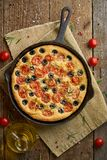 Focaccia, pizza in skillet, italian flat bread with tomatoes, olives and rosemary. Vertical, wooden table. Focaccia, pizza in skillet, italian flat bread with royalty free stock images