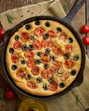 Focaccia, pizza in skillet, italian flat bread with tomatoes, olives and rosemary. Vertical, wooden table. Focaccia, pizza in skillet, italian flat bread with royalty free stock photography