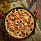 Focaccia, pizza in skillet, italian flat bread with tomatoes, olives and rosemary. Wooden table. Focaccia, pizza in skillet, italian flat bread with tomatoes royalty free stock photography