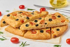 Focaccia, pizza, slice of italian flat bread with tomatoes, olives and rosemary. Focaccia, pizza, slice of italian flat bread with tomatoes, olives and a royalty free stock photo