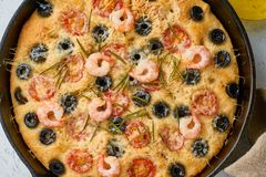 Focaccia, shrimp pizza in skillet. Close up italian flat bread with tomatoes, olives and rosemary. Top view, white concrete. Focaccia, shrimp pizza in skillet royalty free stock photography