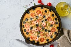 Focaccia, shrimp pizza in skillet, italian flat bread with tomatoes, olives and rosemary. Top view, copy space, white concrete. Focaccia, shrimp pizza in skillet stock photos