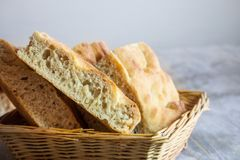 Italian bread of Focaccia Genovese type on display on a basket on a wooden table, sliced in squared pieces. The focaccia is a traditional oven baked flat bread royalty free stock photo