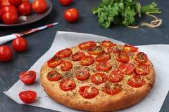 Focaccia z czereśniowymi pomidorami lokalizuje na pergaminie na ciemnym tle obraz stock