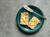 Focaccina al latte del grano intero con burro di fusione sul piatto con il coltello Fotografie Stock