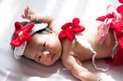 Focalisez au bébé nouveau-né asiatique avec la petite sirène de costumes dans la couleur rouge près de la fenêtre avec la lumière Photos libres de droits