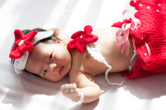 Focalisez au bébé nouveau-né asiatique avec la petite sirène de costumes dans la couleur rouge près de la fenêtre avec la lumière Photos stock