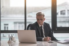 Focalizado aposente-se o trabalhador masculino que datilografa no dispositivo imagens de stock royalty free