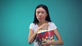 Focalizado na pipoca de devoramento da mulher do filme do copo de papel grande, comer insalubre filme