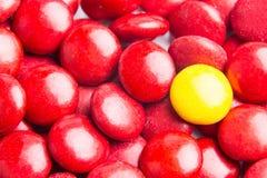 Focalize em doces de chocolate amarelos contra montões de doces vermelhos Fotos de Stock Royalty Free