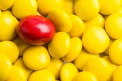 Focalize em doces de chocolate vermelhos contra montões de doces amarelos Fotografia de Stock Royalty Free
