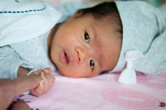Focalize no bebê asiático com chapéu cinzento ao dormir e ao jogar na cama/próximo acima em recém-nascido bonito está olhando a c Fotos de Stock Royalty Free