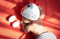 Focalize no bebê recém-nascido asiático com a galinha dos trajes com os dois ovos ao lado da janela com luz solar Fotos de Stock Royalty Free