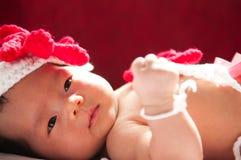 Focalize no bebê recém-nascido asiático com a sereia pequena dos trajes na cor vermelha ao lado da janela com luz solar Fotos de Stock Royalty Free