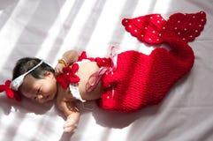 Focalize no bebê recém-nascido asiático com a sereia pequena dos trajes na cor vermelha ao lado da janela com luz solar Fotografia de Stock