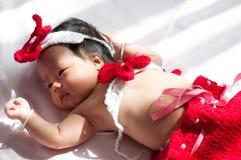 Focalize no bebê recém-nascido asiático com a sereia pequena dos trajes na cor vermelha ao lado da janela com luz solar Imagem de Stock