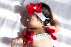 Focalize no bebê recém-nascido asiático com a sereia pequena dos trajes na cor vermelha ao lado da janela com luz solar Foto de Stock