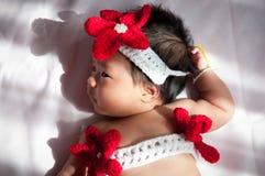 Focalize no bebê recém-nascido asiático com a sereia pequena dos trajes na cor vermelha ao lado da janela com luz solar Fotos de Stock