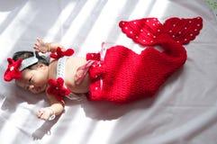 Focalize no bebê recém-nascido asiático com a sereia pequena dos trajes na cor vermelha ao lado da janela com luz solar Imagem de Stock Royalty Free