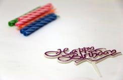 Focalize o sinal do feliz aniversario, o pino para decora o bolo e focaliza para fora a vela colorida para bolos de aniversário Imagem de Stock