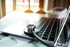 Focalize a tabela do doutor do estetoscópio no laptop com o relatório imagens de stock