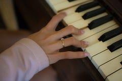Focalize uma mão fêmea que joga o piano de madeira e o seu anel imagens de stock