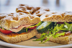 Foccacia sandwich. Foccacia bread as a sandwich with red pesto, rucola salad, cucumber, tomato and sliced ham Royalty Free Stock Images