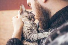 Focinho de um gato e de uma cara do ` s do homem Close-up do homem novo e do gato de gato malhado consideráveis - dois perfis Imagem de Stock