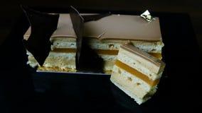 Foco adentro en el pedazo cortado de torta de múltiples capas del caramelo adornada con el chocolate almacen de video
