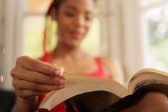 Foco afro-americano do livro de leitura da mulher em casa disponível Foto de Stock