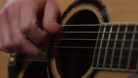Foco bajo de la técnica del juego en la guitarra acústica metrajes