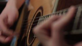 Foco bajo de la técnica del juego en la guitarra acústica almacen de metraje de vídeo