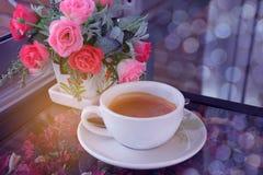 Foco borrado e macio do delicado abstrato um o copo do cappuccino, café quente com a flor, bokeh, luz do feixe, vagabundos do tom fotografia de stock