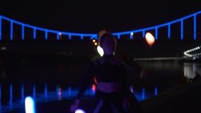 Foco da câmera em dois artistas que gerenciem a probabilidade de intercepção do diodo na noite vídeos de arquivo