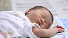 Foco de desplazamiento al bebé Bebé asiático pacífico que miente en una cama mientras que duerme en un dormitorio metrajes