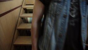 Foco de madera de las escaleras adentro El hombre en la chaqueta, vaqueros, zapatillas de deporte consigue abajo el edificio inte metrajes