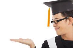 Foco de sorriso do estudante da graduação em sua mão fotos de stock royalty free