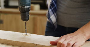 Foco en el carpintero que perfora un tablón de madera almacen de metraje de vídeo