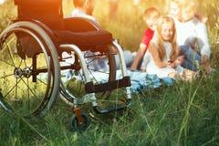 Foco en emply la silla de ruedas en el primero plano mientras que resto feliz de la familia en el fondo imágenes de archivo libres de regalías