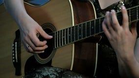Foco en la digitación de los fingeres las secuencias Primer de las manos de una muchacha que toca una guitarra acústica almacen de metraje de vídeo
