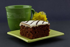 Foco en la torta roja del terciopelo en la placa verde con la taza y el flujo amarillo Imagen de archivo libre de regalías