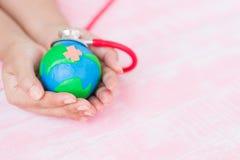 Foco macio da mão da mulher que guarda o globo feito a mão Fotografia de Stock Royalty Free