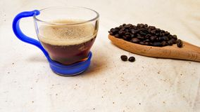 Foco macio de um copo da infusão energética da bebida e dos feijões de café em uma colher de madeira com um fundo cru para a desi Foto de Stock