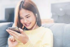 Foco macio do telefone esperto na mão da mulher é usada à escuta a música felizmente Em um momento de abrandamento após o trabalh Imagem de Stock Royalty Free