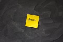 Foco na nota pegajosa amarela de encontro ao quadro-negro Foto de Stock