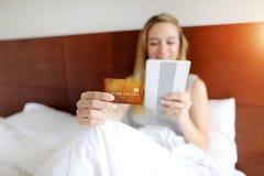 Foco na posse do cartão de crédito pela mulher australiana nova com a tabuleta na luz do sol branca da cama fotografia de stock