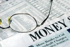 Foco no dinheiro que investe de um jornal foto de stock royalty free