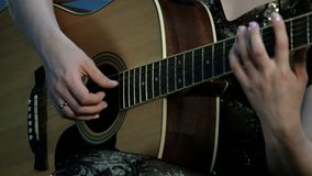 Foco no manejo dos dedos as cordas Close-up das mãos de uma menina que joga uma guitarra acústica vídeos de arquivo